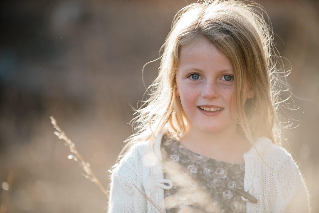 girl smiling near grass