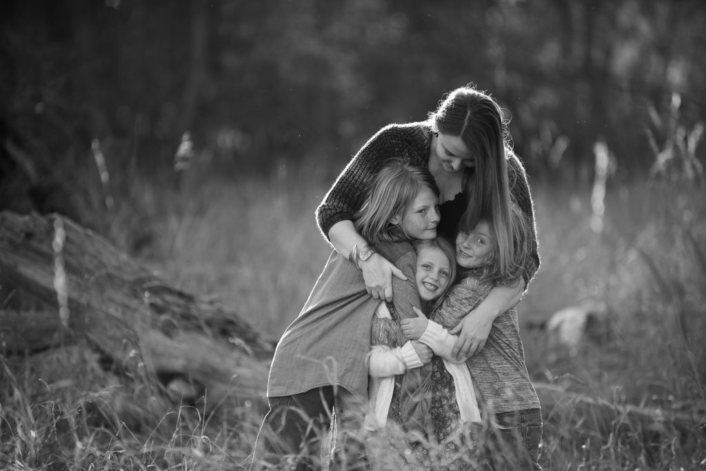 family hugging along the poudre river in fort collins, colorado