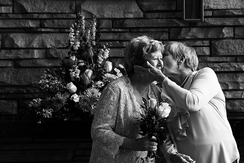 sister kissing bride on cheek