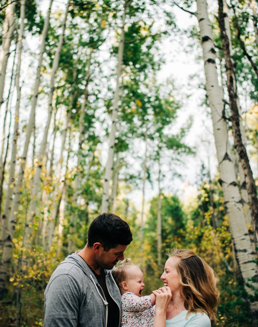 family holding baby and laughing in aspen forest