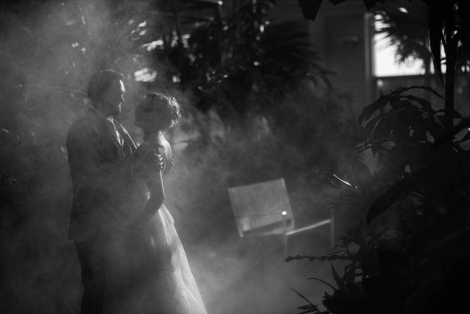 groom holding bride in fog