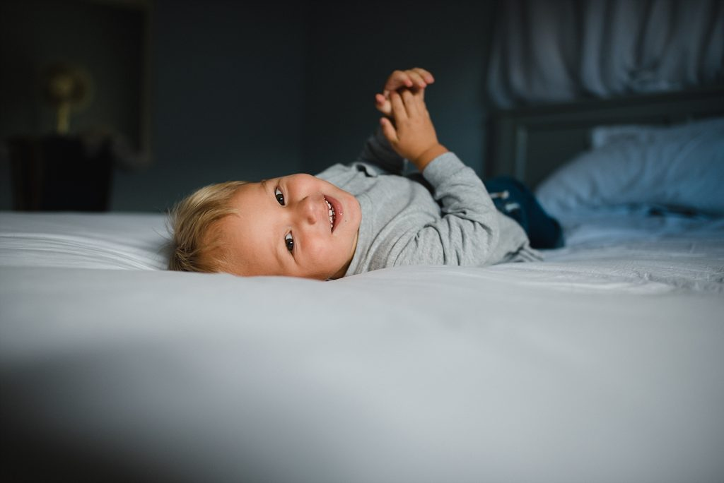 brother smiling and laughing on bed