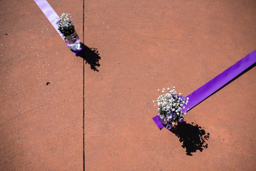 purple flowers in mason jars on concrete