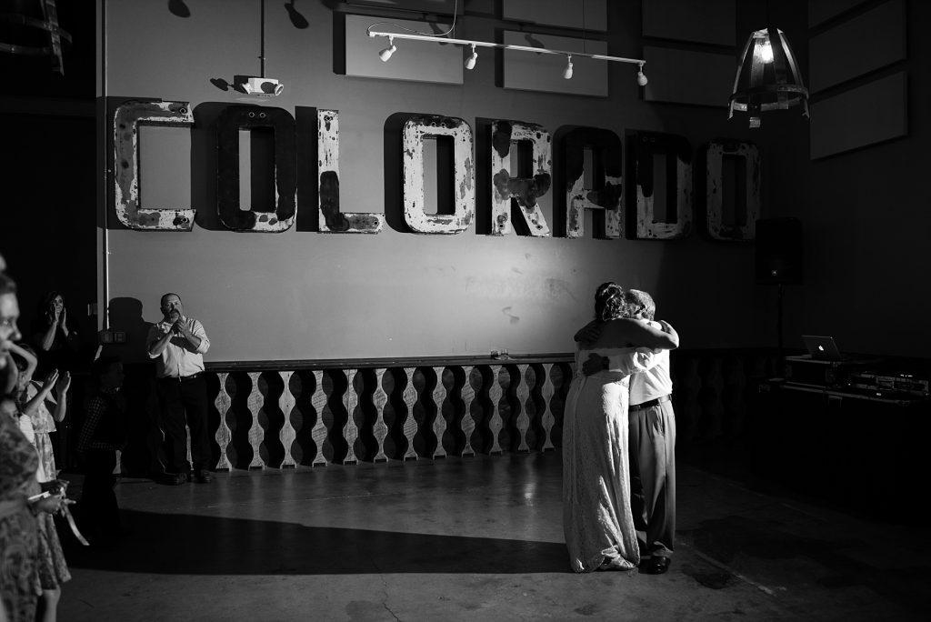bride hugging dad under colorado sign