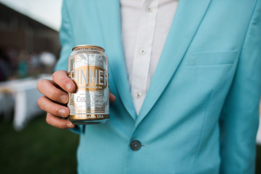 man in blue suit holding oskar blues pinner