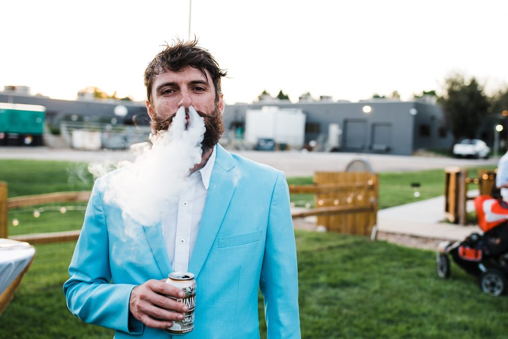 man in blue suit blowing cigar smoke out nostrils