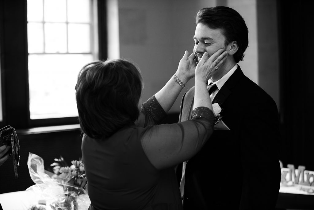 mother of groom touching his face