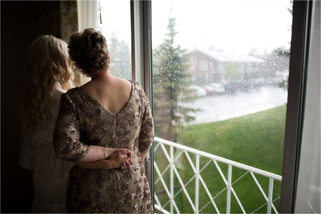 Bride and mom looking out rainy window, photographed on Nikon 28 1.4.
