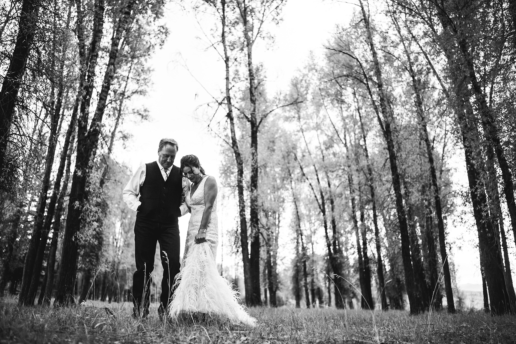 Bride and groom standing in forest