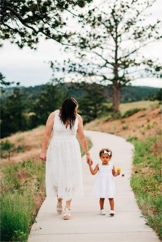 Mom walking down sidewalk, holding hands with daughter.