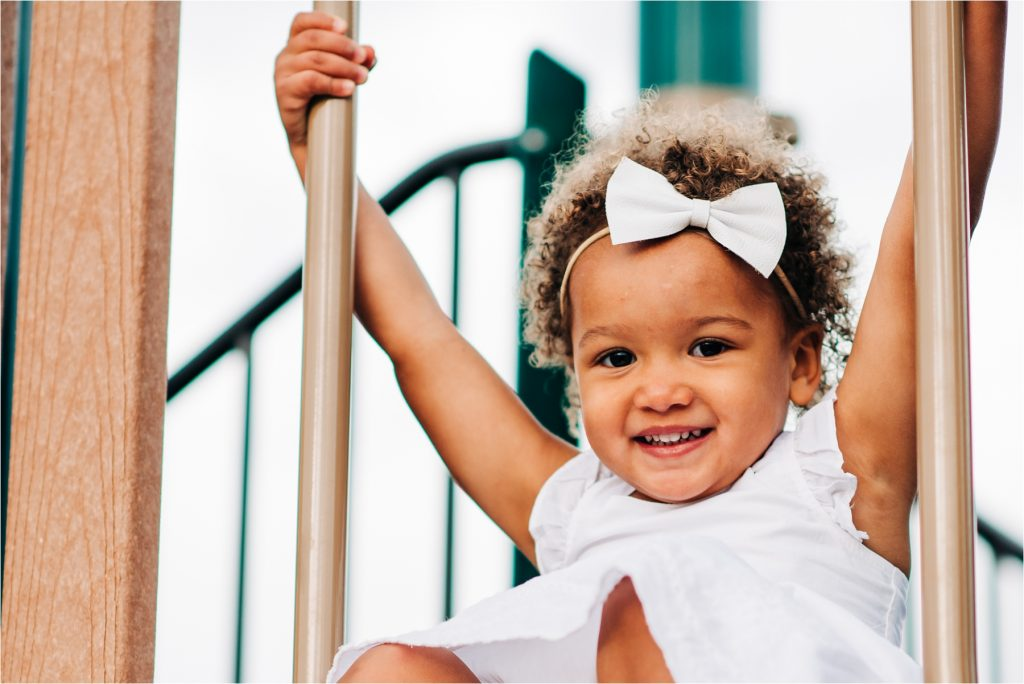 Smiling girl plays on playground equipment.