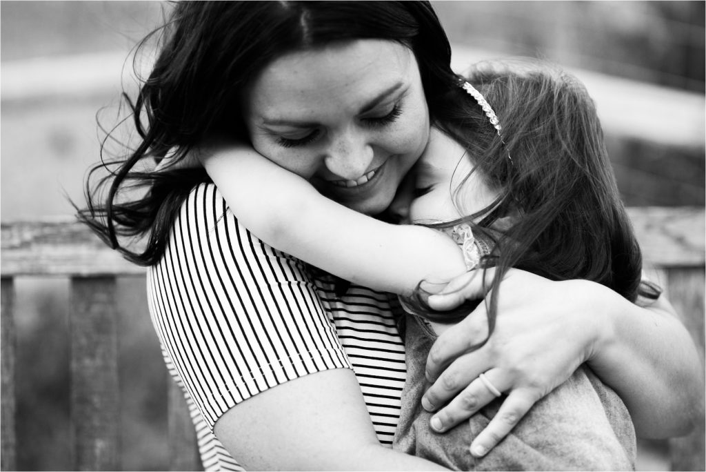 Mom hugging daughter.
